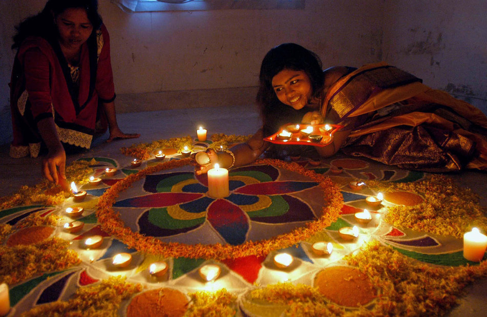 Girls Decorating Diya on Rangoli