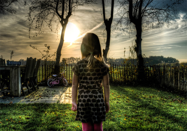 standing alone a beautiful girl front of sun